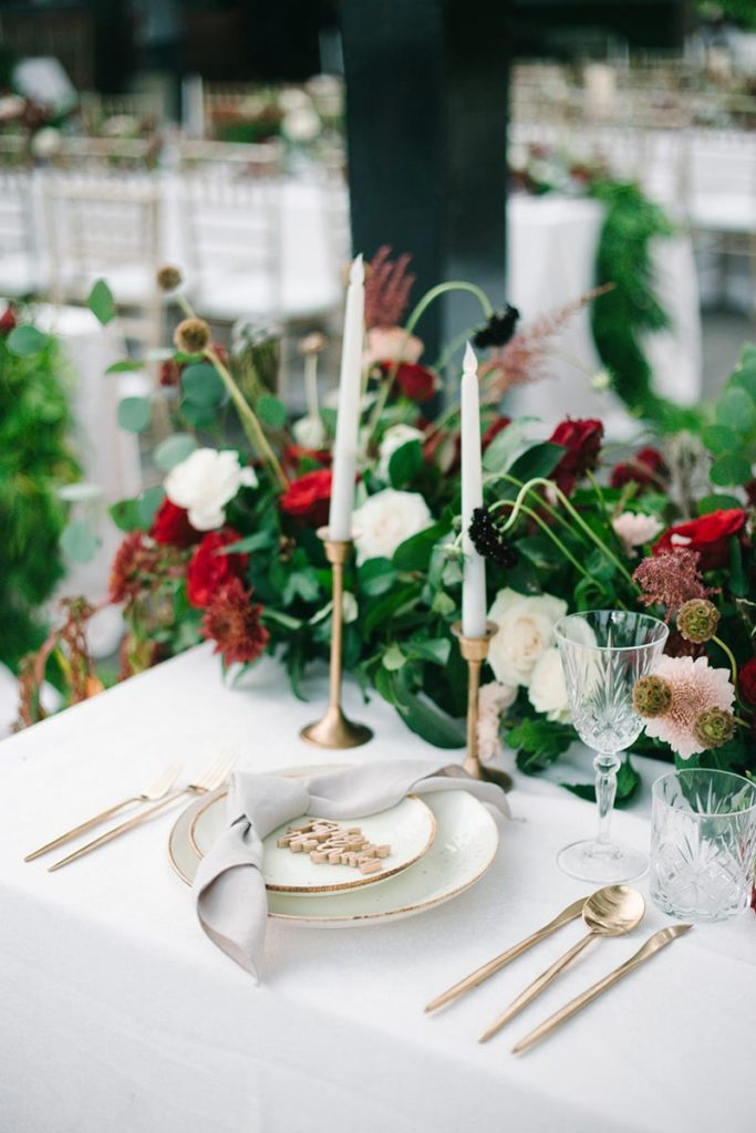 beautiful wedding color scheme with red and white flowers center piece, white plates and gold cutlery